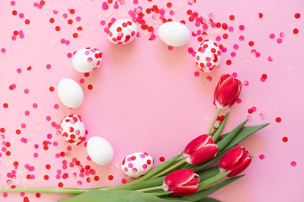 Счастливой пасхи. пасхальные яйца, украшенные бумажным конфетти и тюльпанами