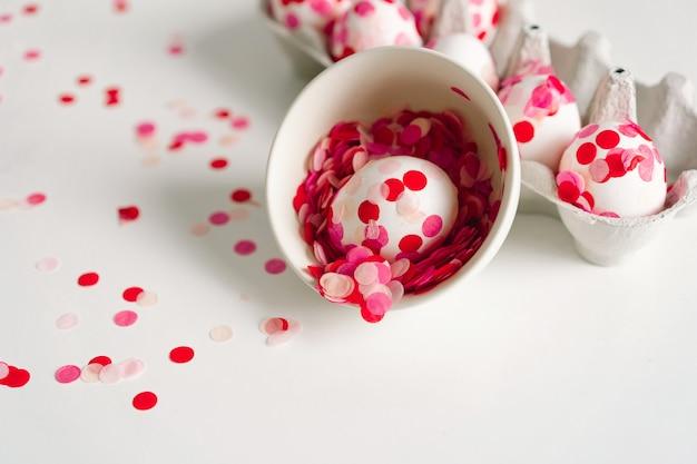 イースター、おめでとう。イースターエッグの装飾ピンクの紙吹雪。春の季節
