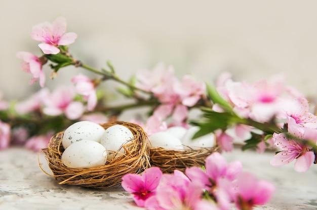 꽃이 만발한 지점의 배경에 계란과 함께 행복 한 부활절 부활절 둥지