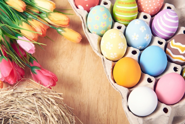Happy easter, easter painted eggs on wooden rustic table for your decoration in holiday. top view with copy space.