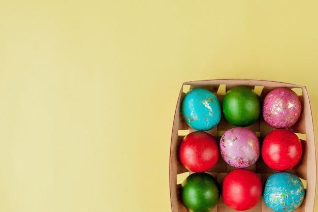 ハッピー イースターの卵は黄色の背景です。グリーティング カード、プロモーション、ポスター用のバスケットに卵が金色に輝いています。スペースをコピーします。