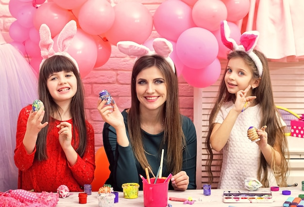 Счастливая семья пасхи красят яйца. пасха, мать и дети в розовых ушках кролика.
