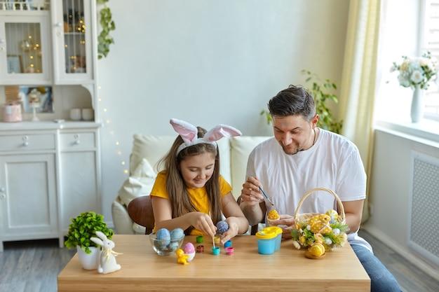イースター、おめでとう。家族は家で卵を描いた。バニーの耳をかぶった父と娘