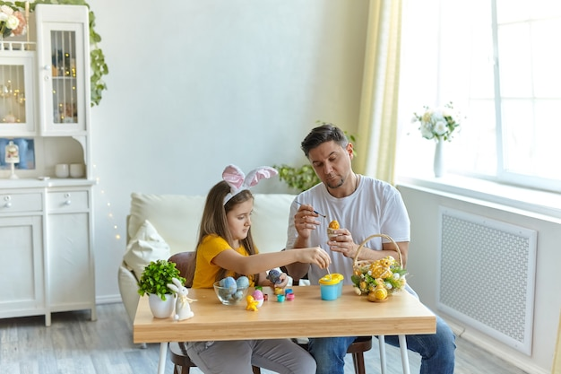 Happy easter. family painted eggs at home. father and daughter wearing bunny ears