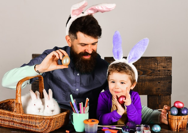 Happy easter. father and son painting easter eggs together.