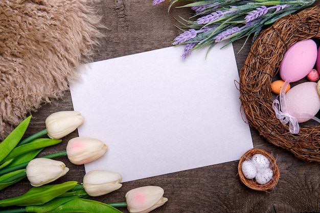 Happy easter frame with greeting card for text, eggs, ribbon bows and flowers on wooden background. easter greeting card.