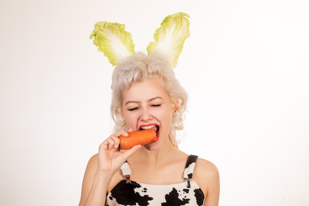 Happy easter and funny easter day. young woman wearing bunny ears on easter day. surprised bunny woman eat carrot.