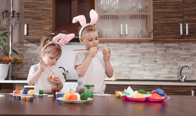 Happy easter. funny and happy children a boy and a girl with bunny ears play, prepare for the holiday and paint eggs.