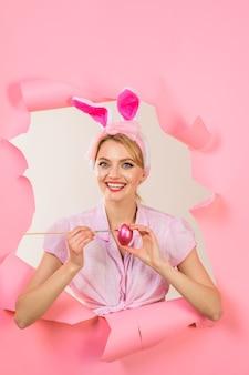 Счастливой пасхи смешная женщина с кроличьими ушками рисует яйцо пасхальная концепция белый кролик идеи пасхального яйца