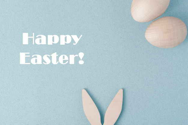 Happy easter greeting card. on a blue background, congratulations on easter. the rabbit's ears stick out at the bottom. there are two eggs at the top.