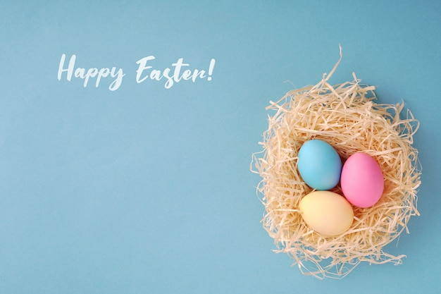 Happy easter greeting card; colored eggs in a hen nest.