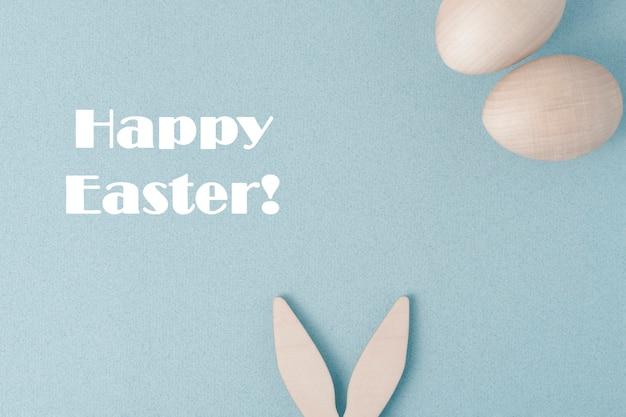 행복 한 부활절 인사말 카드입니다. 파란색 배경에 부활절을 축하합니다. 토끼의 귀가 바닥에 튀어 나와 있습니다. 상단에 두 개의 계란이 있습니다.