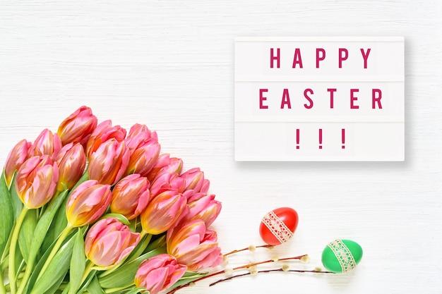 卵とピンクのチューリップとハッピーイースターグリーティングカード