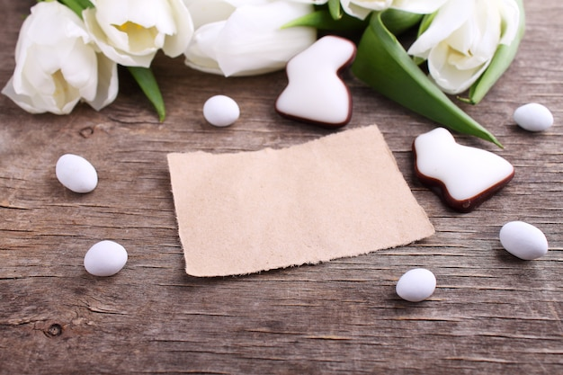 Happy easter greeting card with white tulip and chocolate eggs and bunny, rustic background.