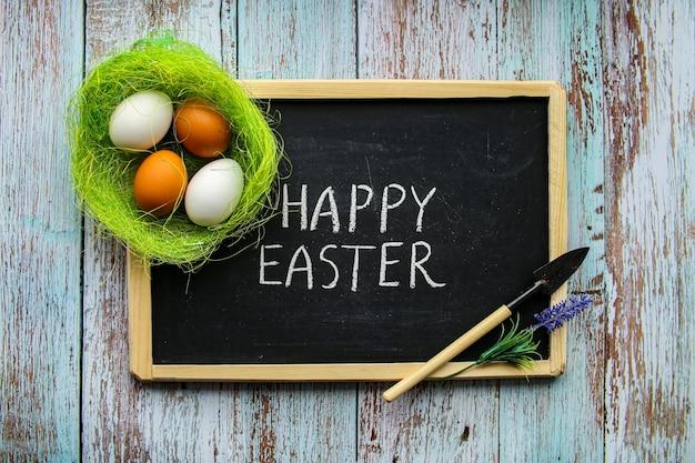 Счастливый состав праздника пасхи с пасхальными яйцами в гнезде на голубой предпосылке. вид сверху, плоская планировка. фото высокого качества