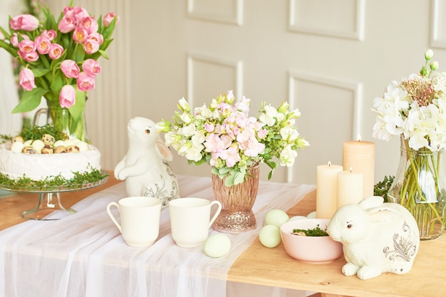 Happy easter! holiday decorations. beautiful festive easter table setting with bunny, flowers and eggs. spring color theme, copy space.easter greeting card template. kitchen interier.