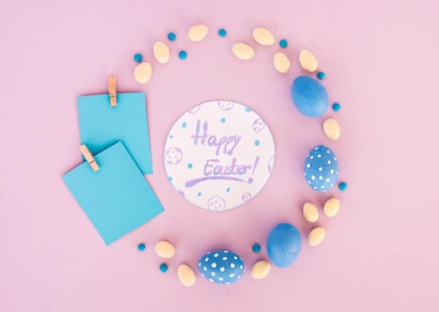 着色された卵と紙と紙の上のハッピーイースターの碑文