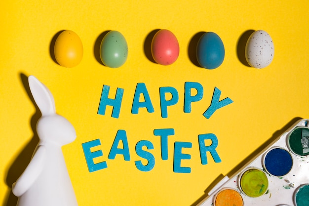 Happy easter inscription with eggs and rabbit on table