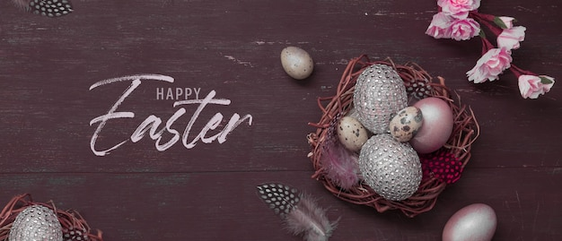 Happy easter inscription with nest and eggs on wooden with pink blossom flowers flat lay. greeting happy easter banner