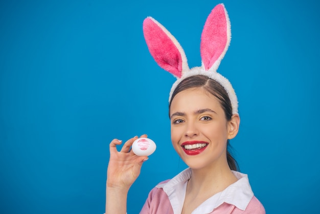 Happy easter. lips and easter, lipstick kiss imprint on easter egg. young woman in rabbit bunny ears
