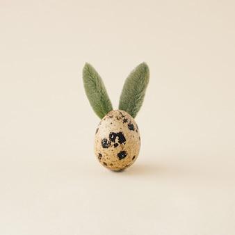 Счастливой пасхи минимальная концепция. уши кролика кролика из натуральных зеленых листьев на яйце на пастельном фоне. плоская планировка.
