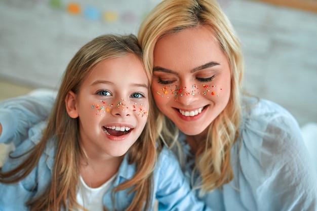 Христос воскрес! мама и дочка на кухне развлекаются разноцветными конфетными украшениями, готовясь к празднику.