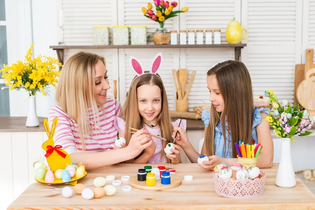 Happy easter. mom and daughters draw easter eggs. a happy family is preparing for easter.