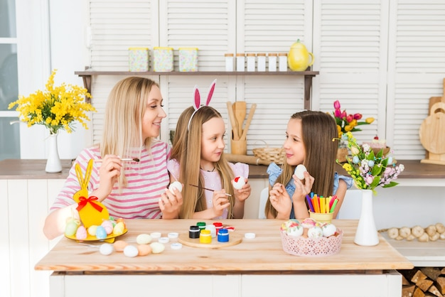 Happy easter. mother and daughters draw easter eggs. a happy family is preparing for easter.