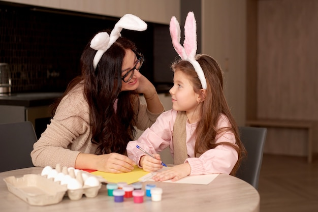 Happy easter! a mother and her daughter painting easter eggs.