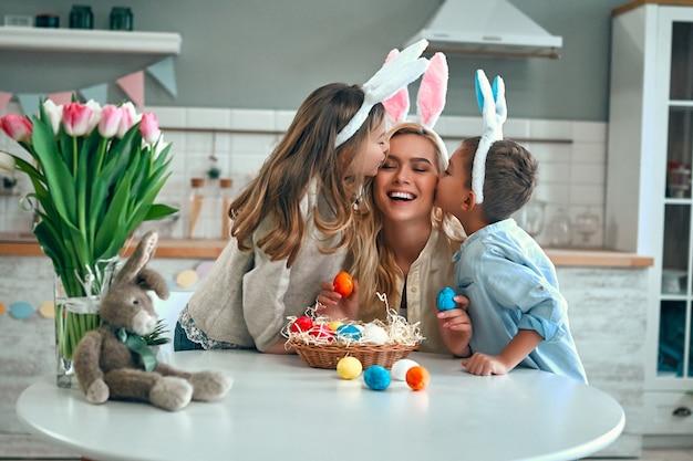 행복한 부활절! 어머니, 아들, 딸이 부활절 달걀을 찾기 시작합니다. 아이들은 아름다운 어머니의 뺨에 키스합니다. 부활절 날 토끼 귀를 입고 귀여운 작은 소년과 소녀.