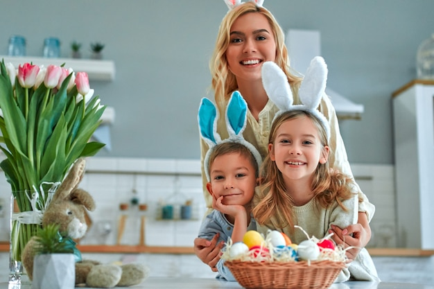 행복한 부활절! 어머니, 아들, 딸이 부활절 달걀을 찾기 시작합니다. 부활절을 준비하는 행복 한 가족. 부활절 날 토끼 귀를 입고 귀여운 작은 소년과 소녀.