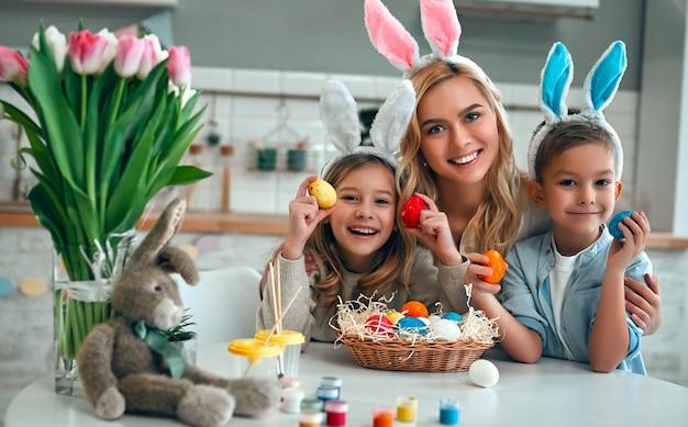 Счастливой пасхи! мать, сын и дочь начинают охоту за пасхальными яйцами. счастливая семья готовится к пасхе. милый маленький мальчик и девочка в ушах зайчика в день пасхи.