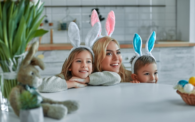 Happy easter! mother, son and daughter begin to hunt for easter eggs. happy family preparing for easter. cute little boy and girl wearing bunny ears on easter day.