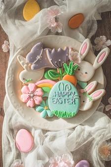 행복한 부활절. 나무 테이블에 여러 가지 빛깔 된 파스텔 부활절 쿠키입니다. 부활절 개념