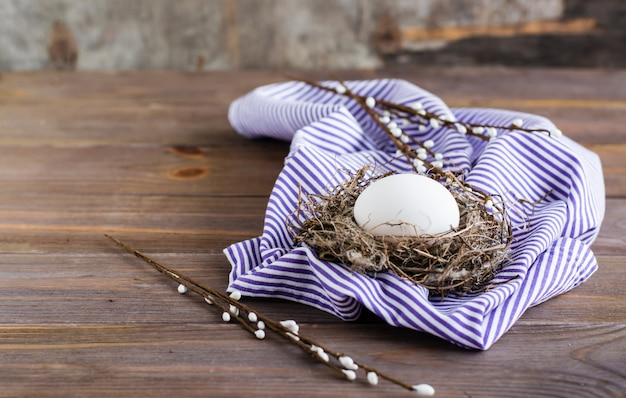 Happy easter. one unpainted chicken egg in a bird's nest and willow branches on a wooden table. .