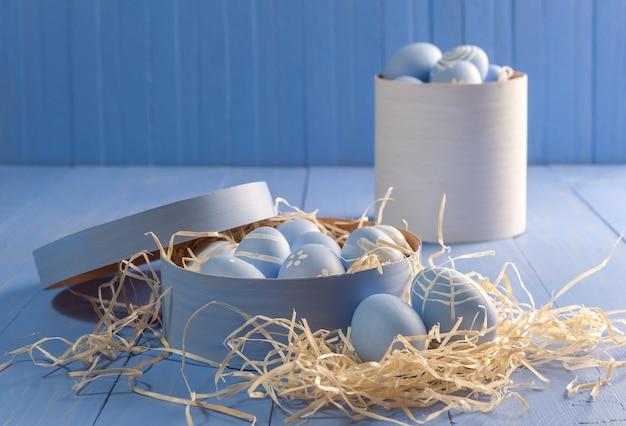 ハッピーイースターは、木製のカラフルなテーブルに卵を描いた。コピースペース