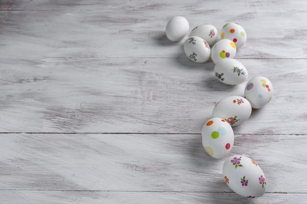 ハッピーイースターは、木製のカラフルなテーブルに卵を描いた。卵狩り、コピースペース