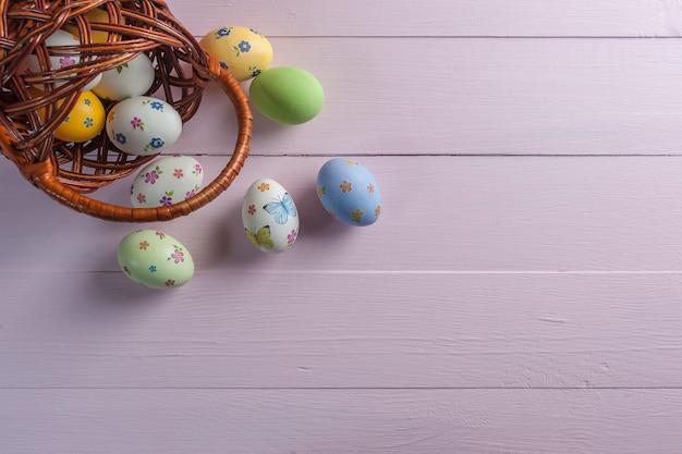 幸せなイースターはあなたの装飾のための木製のカラフルなテーブル、休日の背景に卵を描いた。コピースペース