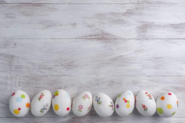 あなたの装飾のための木製のカラフルなテーブル、休日の背景に幸せなイースター塗装卵。