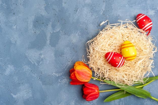 あなたのカードの休日の背景、木製のカラフルなテーブルに花と幸せなイースター塗装卵。卵狩り、コピースペース