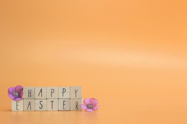 紫色の春の花と木製の立方体のハッピーイースターの引用
