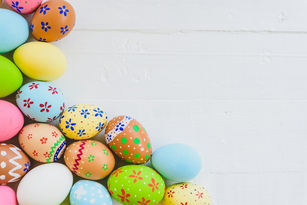 Happy easter! row colorful easter eggs on white wooden background.