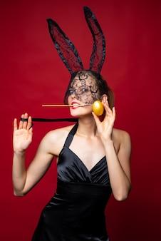 ハッピーイースター赤い背景にバニーの耳を持つセクシーな女性。イースター休暇のコンセプト。