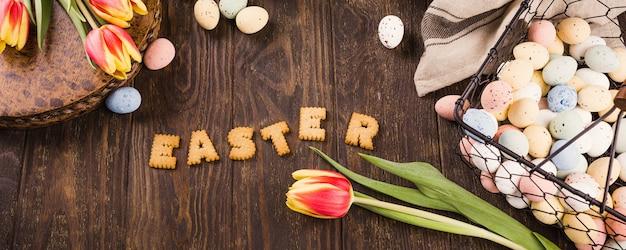 Счастливой пасхи поверхность, надписи из печенья, тюльпанов и красочные перепелиные яйца в металлической корзине на деревянной поверхности. баннер