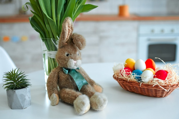 イースター、おめでとう!休日のために飾るテーブル。かごの中のカラフルな卵とチューリップの花束とぬいぐるみのウサギの背景。