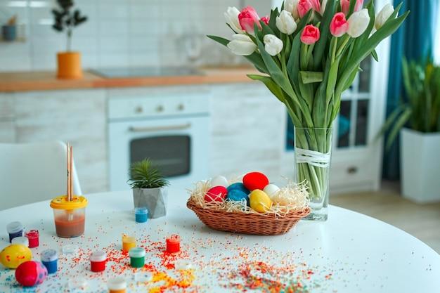 イースター、おめでとう!休日のために飾るテーブル。かごの中のカラフルな卵の背景には、装飾用のテーブルに散らばっているお菓子とチューリップと卵の絵の具の花束。