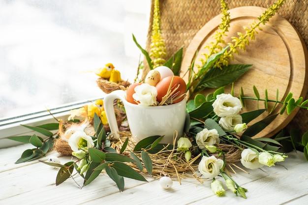 ハッピーイースターテーブル。窓の近くの花の装飾が付いている巣のイースターエッグ。ウズラの卵。ハッピーイースターのコンセプト