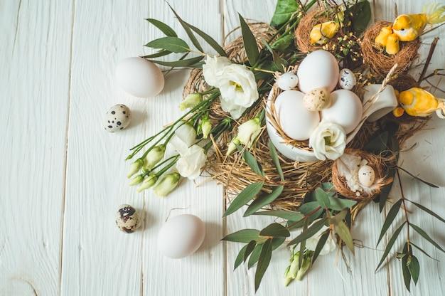 ハッピーイースターテーブル。花飾り付きの木製の白いテーブルの上にカップのイースターエッグ。ハッピーイースターのコンセプト