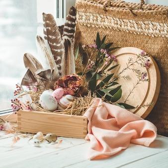 ハッピーイースターテーブル。花の装飾と窓の近くの羽の巣でピンクのイースターエッグ