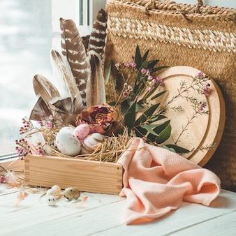 Happy easter table. pink easter eggs in a nest with floral decorations and feathers near the window